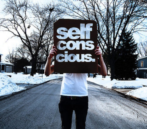 man holding self conscious sign